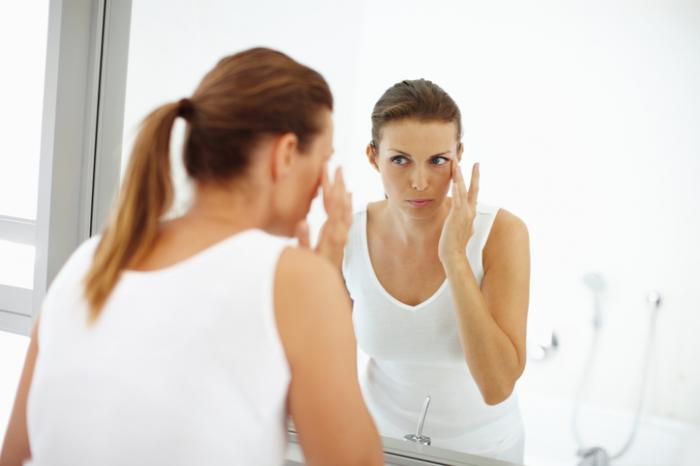 A woman is applying eye lotion.