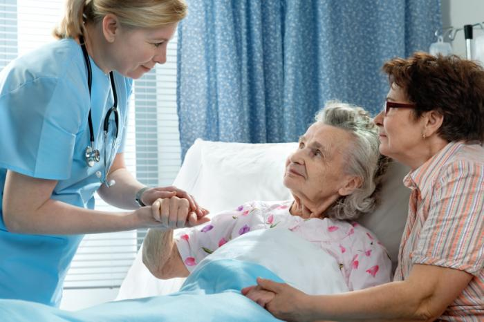 older lady in hospital attended by nurse, relative
