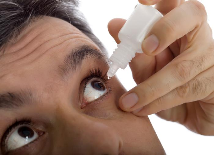 A man administer s eye drops into his left eye